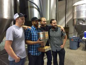 Bosque's brewing staff poses with the IPA Challenge trophy. From left, head brewer John Bullard, assistant brewers Ira Strain-Bey and Ryan Jameson, and founding brewer Gabe Jensen.