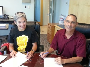 Los Alamos Beer Co-op president Micheline Devaurs signs the lease for the brewery's new space downtown.