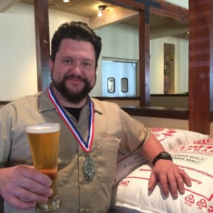 Chama River brewer Zach Guilmette poses with his GABF gold medal and Class VI Golden Lager. (Photo courtesy of Chama River)