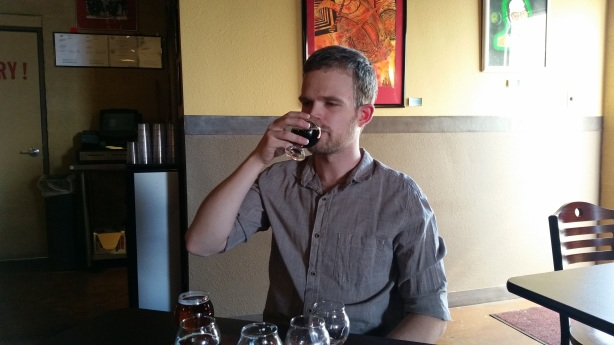 Will Brennand samples the beers at Red Door that they brewed since he left to pursue a masters degree in England.